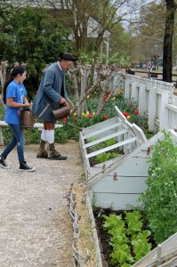 Wesley Greene watering with a Williamsburg visitor.