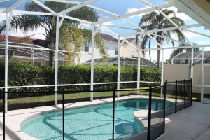 The villa's pool is enclosed in a lanai and has a patio table for outdoor dining.