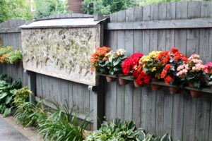 Check out the bright begonias and artwork that dress up this stockade fence in Carol Siracuse and Tom Palamuso's back yard.
